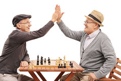 Seniors playing chess and high-five each other Stock Images