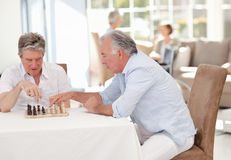 Seniors playing chess in the living room Royalty Free Stock Photo