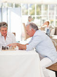 Seniors playing chess in the living room Royalty Free Stock Images