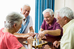 Seniors playing chess. In a retirement home stock photo