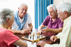 Seniors playing chess. In a retirement home royalty free stock image