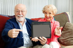 Seniors Point to Tablet PC. Senior couple pointing to a message on their tablet PC Stock Photography