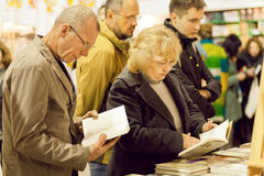 Seniors reading new books with interest Stock Images