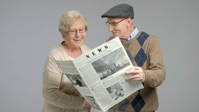 Seniors reading a newspaper and smiling stock footage
