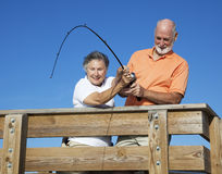 Seniors Reeling in a Big Fish Royalty Free Stock Images