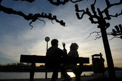Seniors relaxing silhouette. Senior women at a bench during sunset chatting Royalty Free Stock Photography