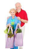 Seniors and Reusable Shopping Bags. Senior couple using reusable shopping bags to bring home their groceries. Isolated on white royalty free stock image