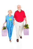 Seniors With Reusable Shopping Bags. Environmentally aware senior couple bringing home groceries in reusable bags. Isolated on white royalty free stock photography