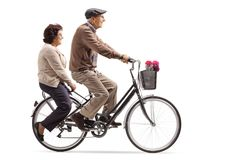 Seniors riding a bicycle together Stock Images