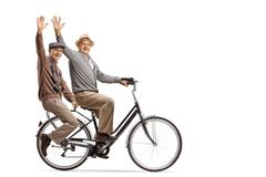 Seniors riding on a bicycle and waving at the camera. Isolated on white background royalty free stock photo
