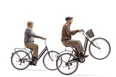 Seniors riding bicycles with one of them doing a wheelie Stock Photography