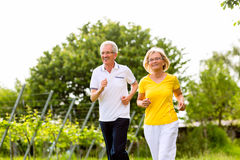 Seniors running in the nature doing sport Stock Photo
