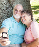Seniors Say Cheese. Senior couple taking their self-portrait with a cellphone camera Royalty Free Stock Photography