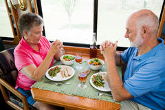 Seniors Saying Grace. Senior couple say grace before eating a meal in their motor home Stock Photos