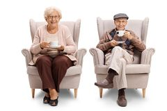 Seniors seated in armchairs drinking tea Royalty Free Stock Photography