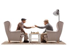 Seniors seated in armchairs playing a game of chess and arguing Stock Photos