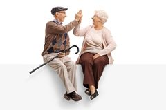 Seniors seated on a panel high-fiving each other. Isolated on white background stock images