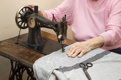 Seniors sew clothes on an old sewing machine. An old white hair woman sews on an old sewing machine Royalty Free Stock Photography