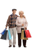 Seniors with shopping bags looking at the camera and smiling Royalty Free Stock Images