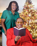 Seniors Sing at Christmas. A senior adult couple singing from a songbook in a Christmas decorated living room Stock Images