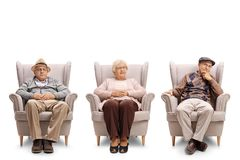 Seniors sitting in armchair and looking at the camera Stock Photos