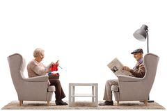 Seniors sitting in armchairs with one of them knitting and the o Stock Images