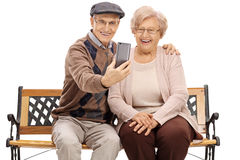 Seniors sitting on a bench and taking a selfie Royalty Free Stock Images