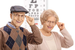 Seniors smiling in front of an eye chart. Isolated on white background stock images
