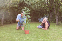 Seniors smoking marijuana and relaxing in the garden Royalty Free Stock Images