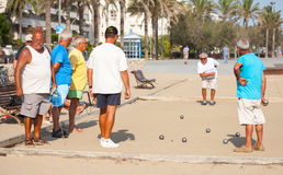 Seniors Spaniards play Bocce on the beach. Calafell, Spain - August 20, 2014: Seniors Spaniards play Bocce on sandy beach in Calafell, small resort town in Stock Photos