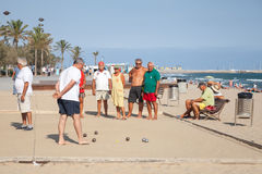 Seniors Spaniards play Bocce on a sandy beach. Calafell, Spain - August 20, 2014: Seniors Spaniards play Bocce on a sandy beach in Calafell, resort town in Royalty Free Stock Photography