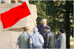 Seniors speaking to each other under red flag. Stock Photo
