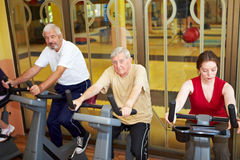 Seniors on spinning bikes Royalty Free Stock Images