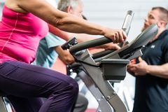 Seniors spinning with personal trainer at the gym royalty free stock photography