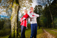 Seniors sports training on a forest road Royalty Free Stock Image