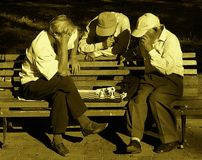 Seniors and strategy - park street chess game. Seniors at an afternoon chess game in the park (Odessa, Ukraine Royalty Free Stock Photo
