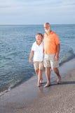 Seniors Stroll on Beach Stock Photo