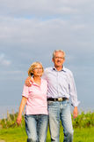 Seniors in summer walking hand in hand Stock Image