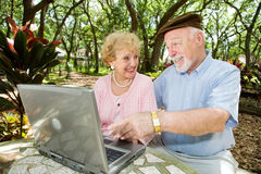 Seniors Surf The Web. Senior couple on their laptop computer in a beautiful, natural setting Royalty Free Stock Photos