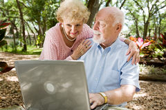 Seniors Surfing the Internet. Senior couple enjoying the computer outdoors in a natural setting Royalty Free Stock Images