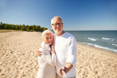 Seniors taking picture with selfie stick on beach Royalty Free Stock Photos