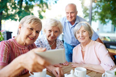 Seniors taking selfie with smartphone. Cheerful seniors gathered together at wooden table for tea party and taking selfie with smartphone Royalty Free Stock Image