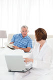 Seniors talking in the bed Royalty Free Stock Images