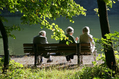 Seniors talking in the park stock images