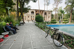 Seniors talking in park near the historical Hasht Behesht Palace in Middle East. Stock Photo
