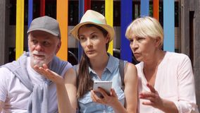 Seniors and daughter sit in park browse in mobile phone. Family look for direction on online map