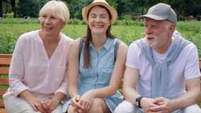 Seniors and their teenage daughter having great time sitting on bench in park chatting relaxing
