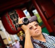 Seniors tourist holding a video camera Stock Images