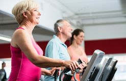 Seniors training on cross trainer with personal trainer at the g Royalty Free Stock Photos