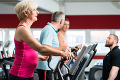 Seniors training on cross trainer with personal trainer at the g Stock Photo